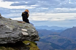Mindfulness. Person sitting on high rock